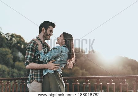 Love at first sight. Beautiful young couple embracing and looking at each other while standing on the bridge outdoors