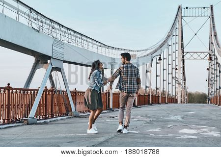 Carefree day together. Full length rear view of playful young couple looking at each other while walking on the bridge outdoors