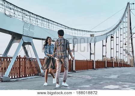 Enjoying time together. Full length of playful young couple holding hands while walking on the bridge outdoors