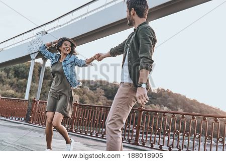 Just for fun. Beautiful young couple holding hands and spinning while dancing on the bridge outdoors