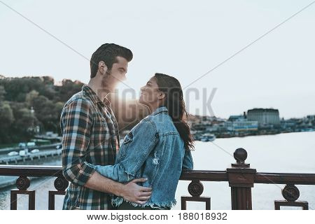 Time stops when she is near. Beautiful young couple embracing and looking at each other while standing on the bridge outdoors