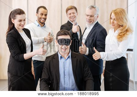 I see nothing. Nice handsome pleasant man sitting on the chair and wearing the eye mask while being surrounded by his colleagues
