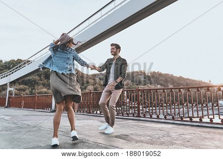 Love is in the air. Full length of playful young couple holding hands and spinning while dancing on the bridge outdoors