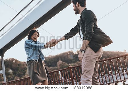 They belong together. Beautiful young couple holding hands and spinning while standing on the bridge outdoors