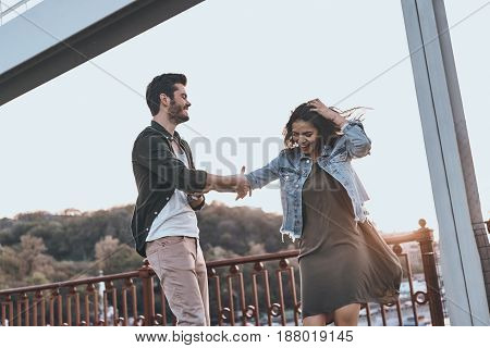 Sunset dance. Beautiful young couple holding hands and spinning while dancing on the bridge
