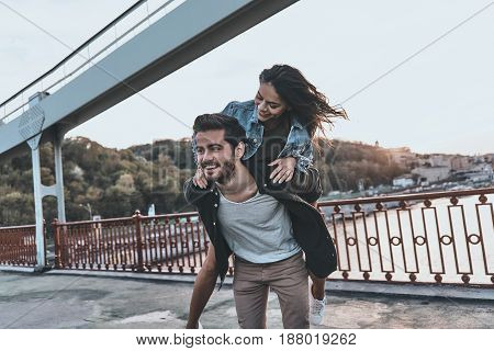 Enjoying every moment together. Young couple having fun outdoors while handsome man giving his girlfriend piggy back ride