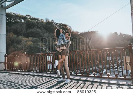 So great to be in love! Full length of handsome man carrying young attractive woman while standing on the bridge outdoors