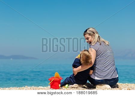 A happy mother and young child boy son having fun on a sunny beach.
