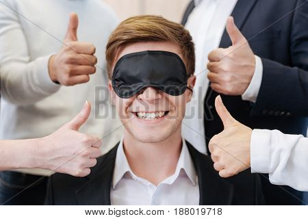 It is awesome. Happy handsome delighted man wearing the sleeping mask and seeing nothing while feeling the support of his colleagues