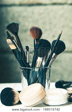 professional brushes in glass in fron of gray wall with powder