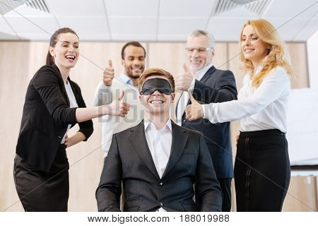 How great. Happy positive nice people standing around their colleague and smiling while showing thumb up gestures