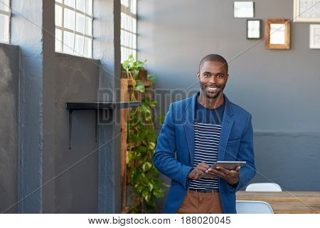 Portrait of a smiling young African businessman standing alone in a large modern office working online with a digital tablet
