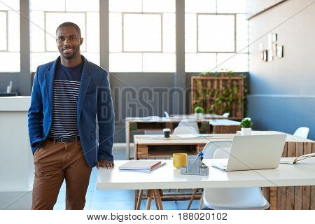 Portrait of a confident young African businessman in a blazer smiling while standing alone in a large modern office