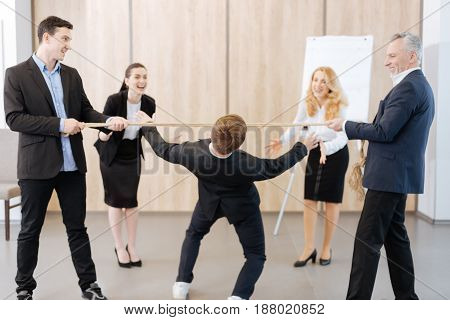Fun activity. Positive happy delighted man standing in the middle of the room and trying to keep balance while going under the rope