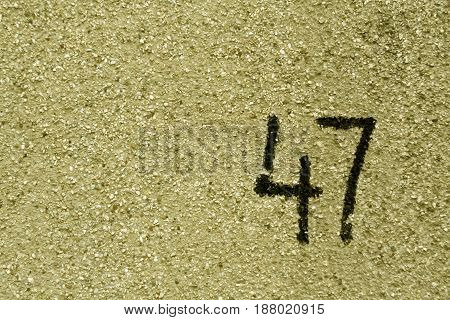 Number Fourty Seven On Yellow Plaster Wall.