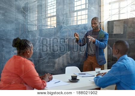 Focused young African businessman giving a presentation to coworkers while standing in front of a chalkboard in a modern office