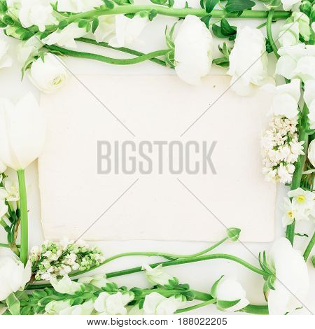 Frame of white flowers - ranunculus, snapdragon and tulip on white background. Background of spring flowers. Flat lay, top view.