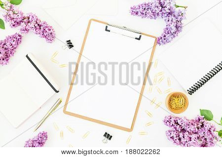 Minimalistic workspace with clipboard, notebook, pen, lilac and accessories on white background. Flat lay, top view. Beauty blog concept