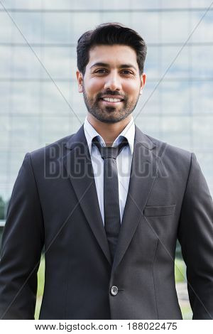 Arabic serious smiling happy successful businessman or worker in black suit with tie and shirt with beard standing in front of an office building.