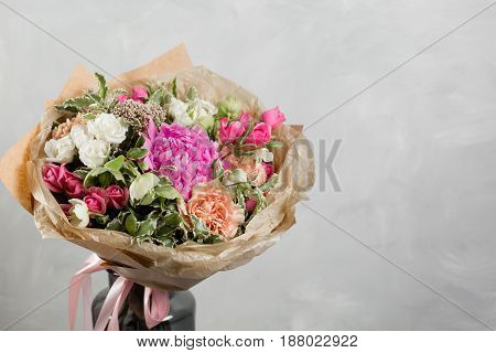Bouquet of different flowers in a mixed arrangement against gray wall on background. Copy space.