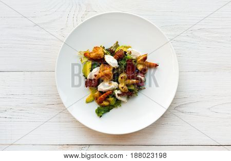 Restaurant food, seafood salad. Traditional italian meal with shrimps and mozzarella on white round plate.