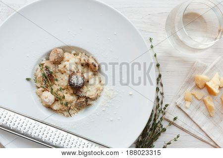 Wild mushrooms porcini risotto with rosemary and fresh grated parmesan cheese. Traditional italian cuisine dish. Restaurant food closeup. Forest fungus with rice. Top view