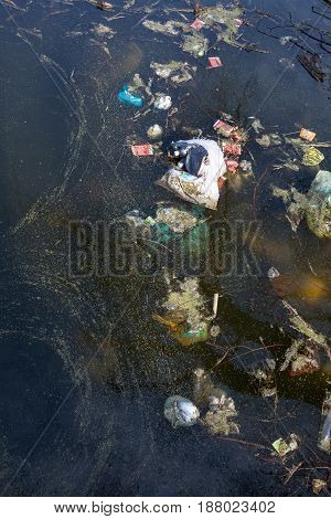 Garbage floating in dirty water. Environmental pollution.