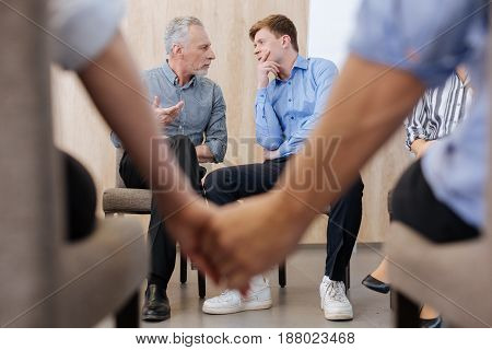 Interaction between people. Nice pleasant positive men sitting together and looking at each other while having a conversation
