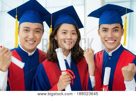 Head and shoulders portrait of cheerful Vietnamese students in graduation gowns and caps doing winner gesture while looking at camera with wide smiles