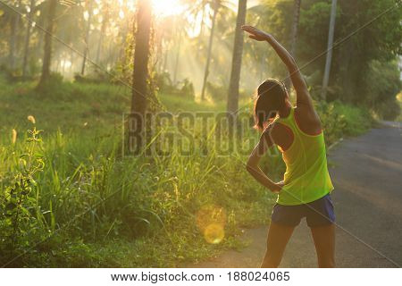 Young female runner warming up before running at morning forest trail