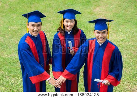 High angle view of smiling Asian graduates joining hands together while standing outdoors and looking at camera