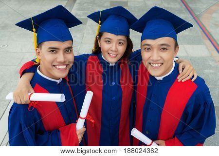 High angle view of enthusiastic Asian friends wearing graduation gowns holding diplomas in hands and posing for photography with wide smiles, waist-up portrait