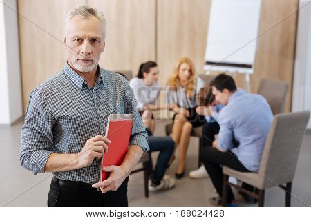 Group psychology session. Handsome nice senior psychologist holding his notes and looking at you while working with a group of patients