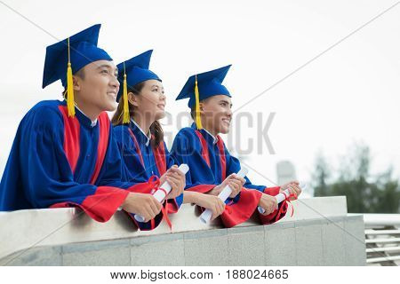 Profile view of enthusiastic graduates looking into distance with smiles while standing on viewing platform, waist-up portrait