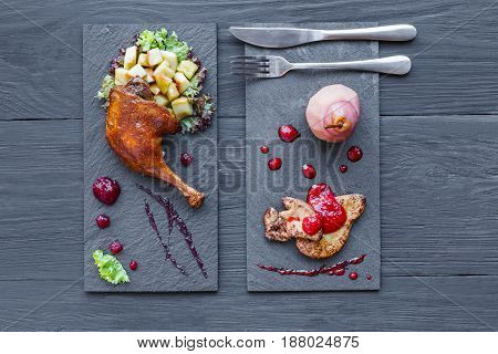 Roasted duck leg and foie gras. Restaurant food on black square slate plates, top view with copy space on wood table background