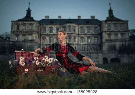 Woman sorceress next to suitcase with flowers on background of ancient castle. She sits on grass.