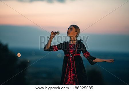 Woman meditates on background of sunset sky. She stands and holds chamomile in her hand.