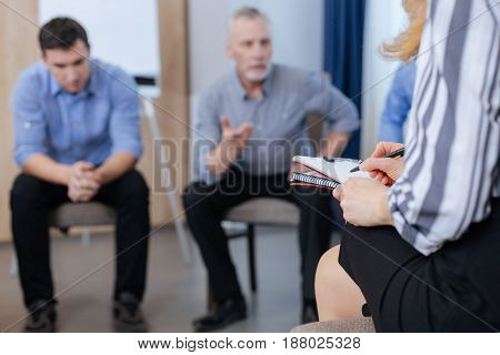 In order not to forget. Selective focus of a professional nice female psychologist sitting on the chair and taking notes while listening to the patient