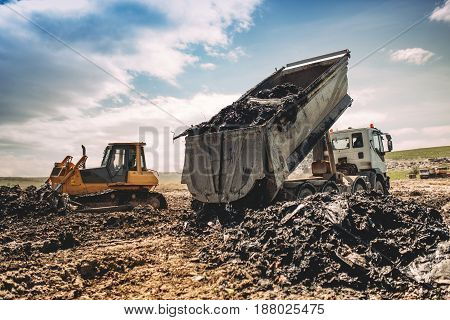 Dumping Truck Unloading Garbage At Dumping Site. Industrial Bulldozer, Excavator And Dumping Trucks