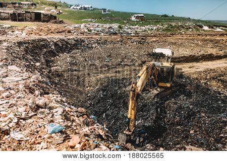 Industrial Excavator Doing Construction Works On Garbage Dumpsite