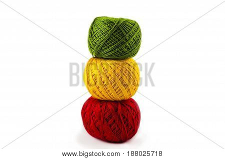 yellow red green balls of cotton threads for knitting on a white background