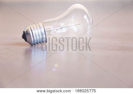 Light bulb close-up lies on a light wooden background