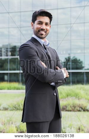 Arabic serious smiling happy successful businessman or worker in black suit with tie and shirt with beard and arms crossed on chest standing in front of an office building.