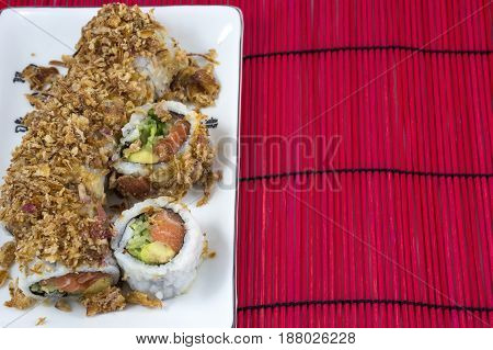 Usual sushi on the white plate on the red bamboo mat
