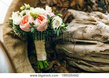 Wedding bouquet on a wooden texture with burlap