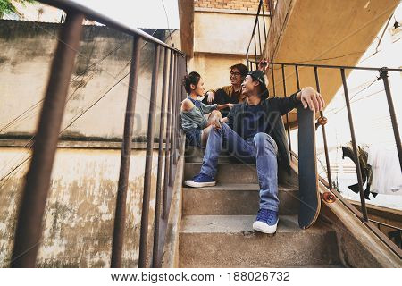 Having fun with friends in urban slums: three Asian friends sitting on stairs and chatting animatedly with each other, low angle view