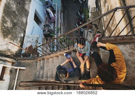 High angle view of stylish Asian teenagers hanging out in urban slums: they sitting on stairs of shabby apartment house and talking to each other