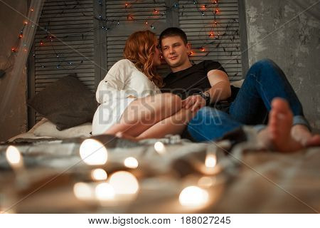 Young enamored woman and man sit side by side on bed and hug. Around them glowing lights.