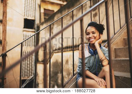 Smiling attractive woman looking at camera with wide smile while enjoying lovely summer day in urban slums, view through steel stair railing