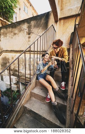 Lovely Asian couple enjoying summer day in urban slums: they sitting on shabby stairs of apartment house and surfing net on modern smartphone